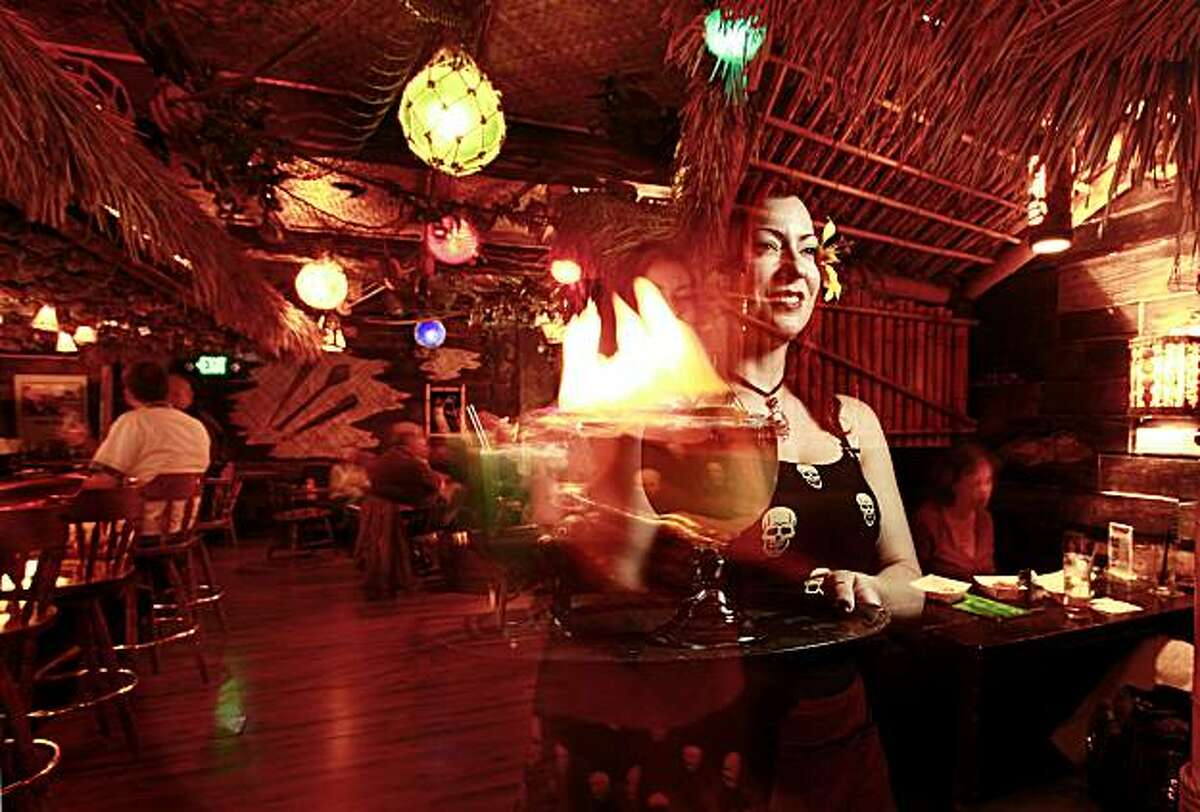 Waitress Lee Williams with a flaming Island Mai Tai, available at the Fobbiden Island Tiki Lounge in Alameda, Calif. on Tuesday July 22, 2009.