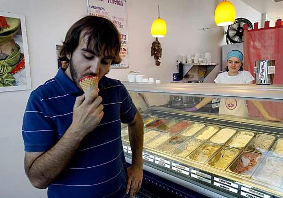 Tom Gartner bites into a cone of strawberry agave ice cream served by Rosa Page (right) at Tara's Organic Ice Cream shop in Berkeley, Calif., on Friday, July 17, 2009. Photo: Paul Chinn, The Chronicle