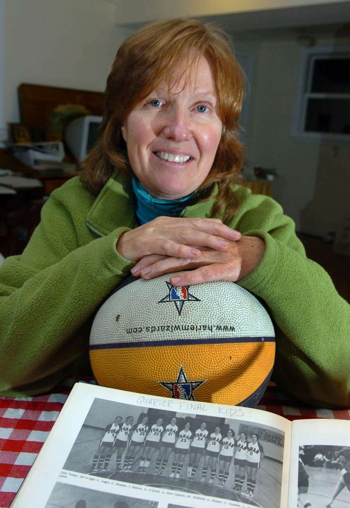 April Hunt was the first female athlete in Connecticut to receive an athletic scholarship to college in 1972. Hunt attened Foran High and held a record until recently. She will be inducted into the state Basketball Hall of Fame later this month. Here, Hunt poses with a basketball and her high school team photo at her home in Milford, Conn. on Friday Nov. 06, 2009.