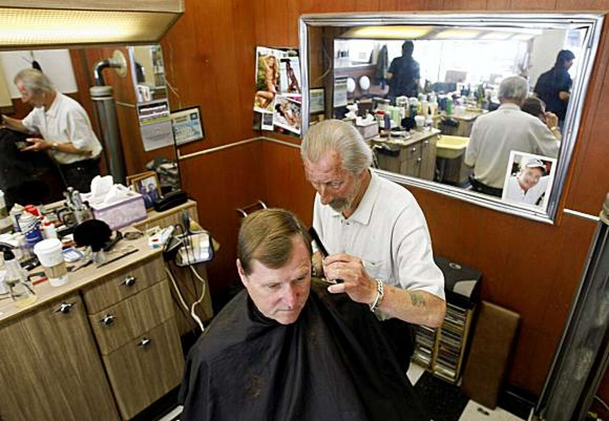 Rocky Becker cuts hair for long-time customer Michael Peters at the Montclair Barber Shop in Oakland, Calif., on Tuesday, July 7, 2009.