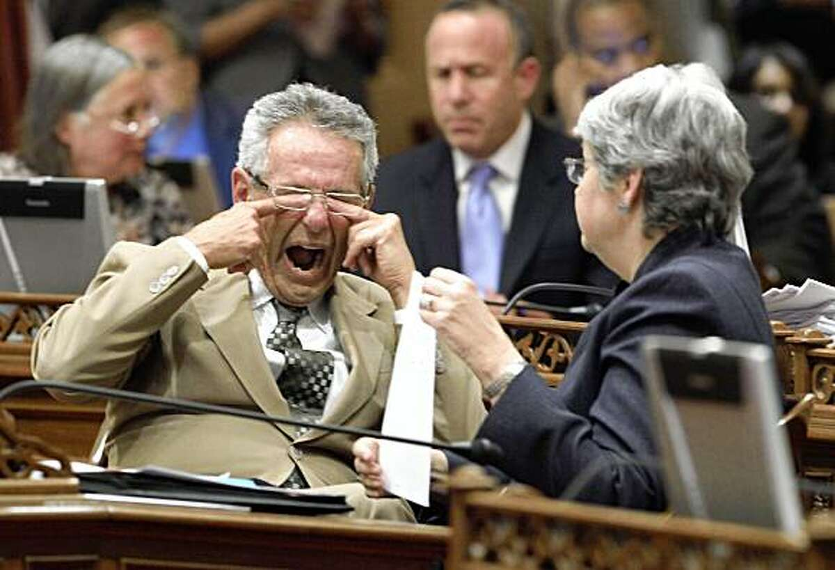 State Sen. Alan Lowenthal, D-Long Beach, rubs his eyes and yawns as he talked with Sen. Christine Kehoe, D-San Diego, during the early morning hours at the Capitol in Sacramento, Calif., Friday, July 24, 2009. Lawmakers worked overnight voting on a package of bills worked out between Gov. Arnold Schwarzenegger and Legislative leaders to resolve the state's $26.3 billion budget deficit.