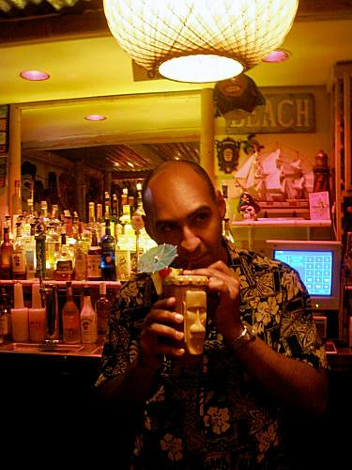 Tiki club owner Michael Thanos enjoys a drink at Conga Lounge in Oakland.