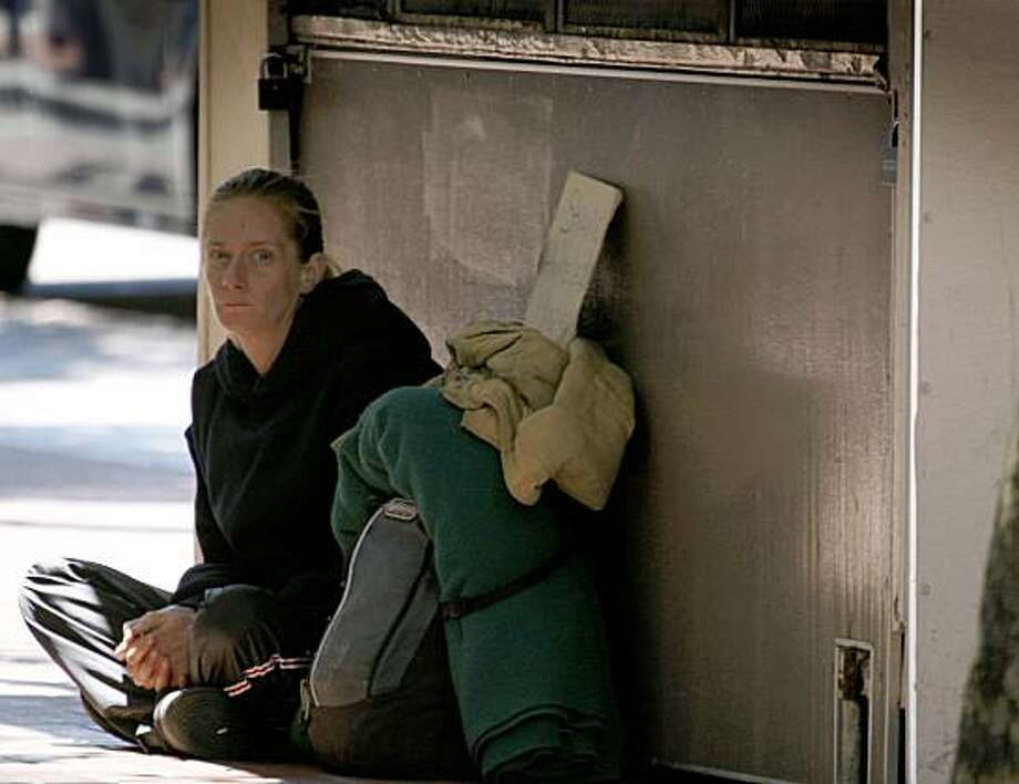 A woman identified as Toni Mills sits in front of an empty flower stand on Market Street in San Francisco, Calif., on Friday, July 17, 2009. Photo: The Chronicle