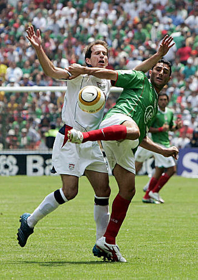 MEXICO CITY - MARCH 27:  Eddie Lewis #7 of the USA tangles with Salvador Carmona #18 of Mexico in the second half during their 2006 FIFA World Cup qualifying match on March 27, 2005 at Estadio Azteca in Mexico City, Mexico. Lewis scored the lone goal for USA in the 2-1 loss to Mexico.  (Photo by Brian Bahr/Getty Images) Photo: Brian Bahr, Getty Images