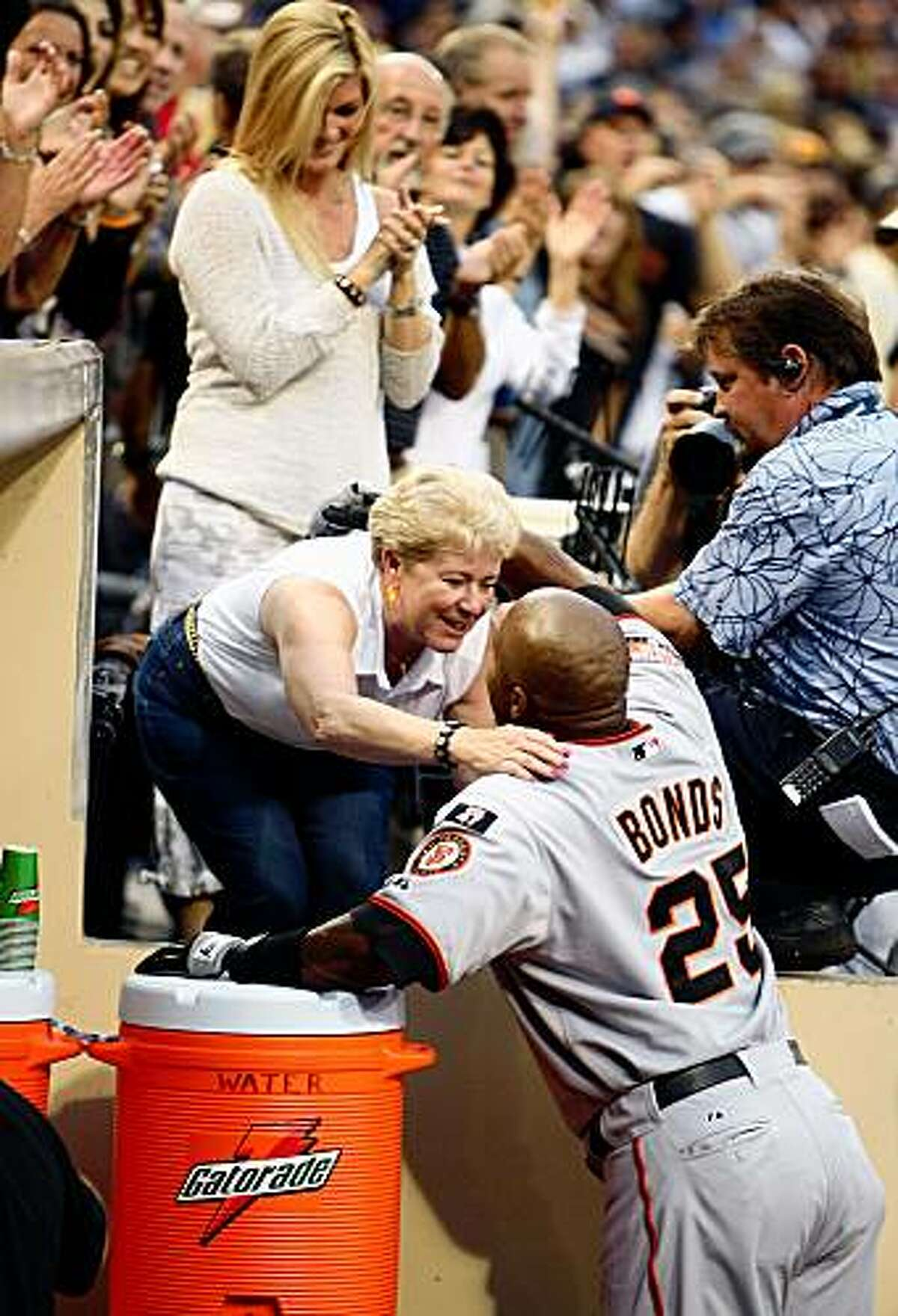 SAN DIEGO - AUGUST 04: Barry Bonds #25 of the San Francisco Giants goes to the far end of the dugout to hug Sue Burns, the wife of late Giants ownership partner Harmon Burns, after hitting career home run #755 in the second inning against the San Diego Padres during a MLB game at Petco Park August 4, 2007 in San Diego, California. Bonds tied Hank Aaron's career all time home run record. (Photo by Donald Miralle/Getty Images)