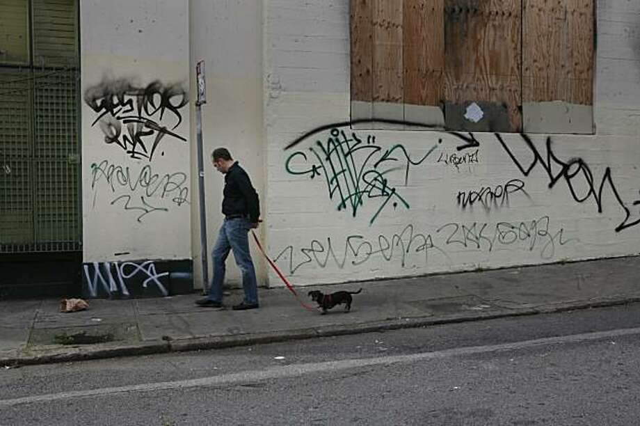 Not from his home, Matthew Kennedy walks his dog Max past the graffiti marked walls of 1050 Howard Street on Tuesday, Mar. 11, 2008 in San Francisco, Calif. The city posted a sign on the front door of 1050 Howard ordering the property owners to clean up the graffiti with 30 days. Residents say the graffiti has been there a lot longer than that. Photo by Mike Kepka / San Francisco Chronicle Photo: Mike Kepka, SFC