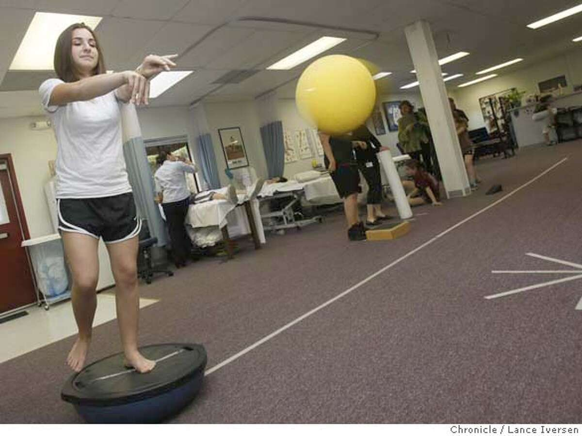 ###Live Caption:Nicole Simon age 15 from Oakland injured both knees, first in Soccer then Basketball that required surgery performs balaces herself on a Bosu Ball drill while tossinga weighted ball. The drill helps strengthen her knees. Simon is now enrolled in a physical Therapy program with Bruce Valentine a certified Athletic Trainer at the new Sports Medicine Center for Young Athletes at Children's Hospital. Photo taken on Thursday March 6, 2008. Photo by Lance Iversen / San Francisco Chronicle###Caption History:Nicole Simon age 15 from Oakland injured both knees, first in Soccer then Basketball that required surgery performs balaces herself on a Bosu Ball drill while tossinga weighted ball. The drill helps strengthen her knees. Simon is now enrolled in a physical Therapy program with Bruce Valentine a certified Athletic Trainer at the new Sports Medicine Center for Young Athletes at Children's Hospital. Photo taken on Thursday March 6, 2008. Photo by Lance Iversen / San Francisco Chronicle###Notes:Lance Iversen 415-2979395###Special Instructions:MANDATORY CREDIT PHOTOG AND SAN FRANCISCO CHRONICLE.