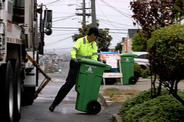 Ismael Martin, who's making 700-800 house stops on Monday, July 28, 2008, picks up compost cans on 33rd Ave. between Lawton and Moraga streets in San Francisco, Calif.  A proposed ordinance from the director of the Department of the Environment would require all San Francisco residents and businesses to begin recycling food scraps and other compostable material.  Photo by Liz Hafalia/The Chronicle Photo: Liz Hafalia, The Chronicle