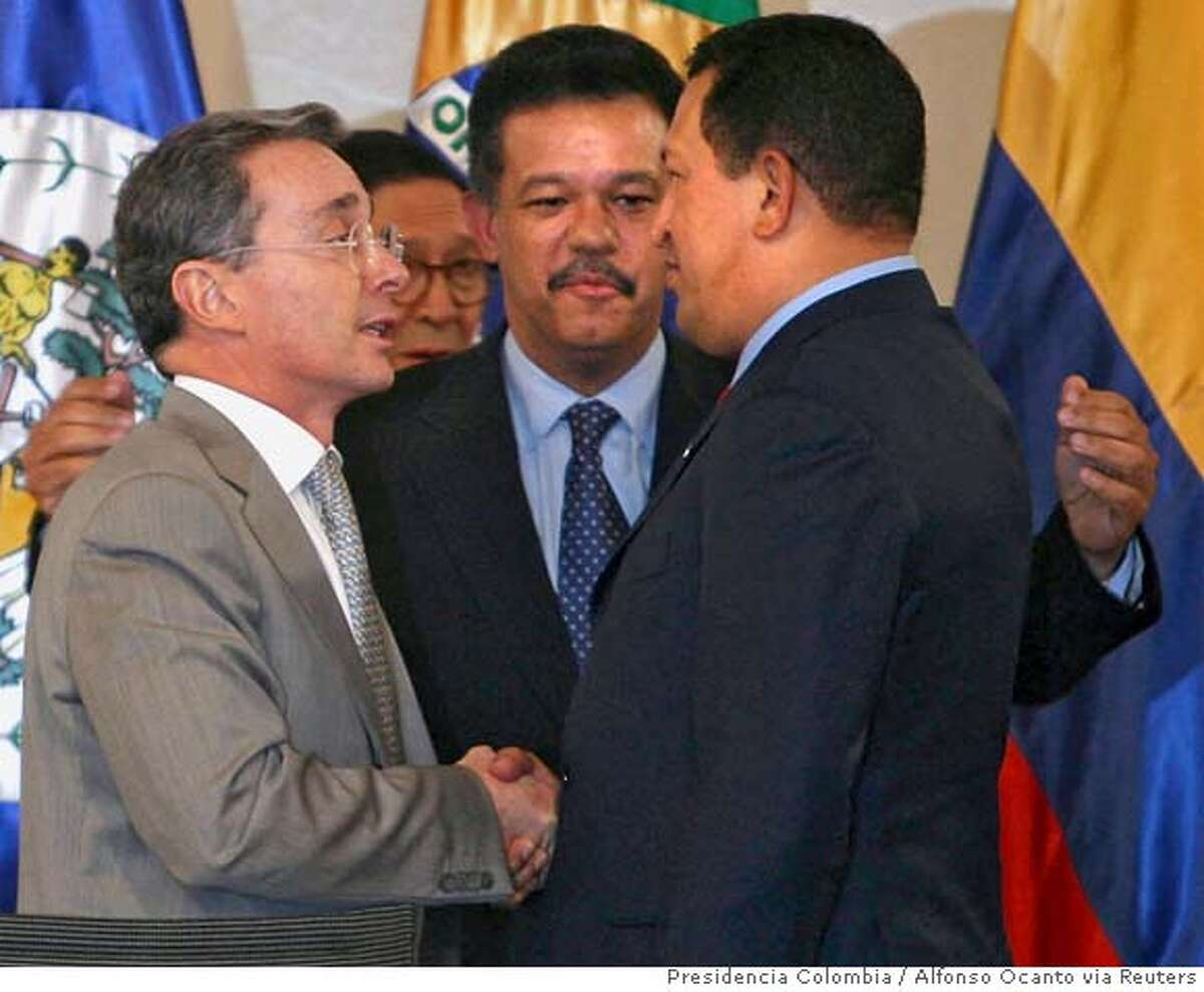 ###Live Caption:Colombia's President Alvaro Uribe (L) and Venezuelan President Hugo Chavez (R) talk, as Dominican President Leonel Fernandez looks on after they agreed to resolve the crisis set off by an attack on a FARC guerrilla camp inside Ecuadorian territory by the Colombian armed forces last week at the 20th Group of Rio Summit in Santo Domingo, March 7, 2008. REUTERS/HO/Presidencia Colombia/Alfonso Ocanto (DOMINICAN REPUBLIC). FOR EDITORIAL USE ONLY. NOT FOR SALE FOR MARKETING OR ADVERTISING CAMPAIGNS..###Caption History:Colombia's President Alvaro Uribe (L) and Venezuelan President Hugo Chavez (R) talk, as Dominican President Leonel Fernandez looks on after they agreed to resolve the crisis set off by an attack on a FARC guerrilla camp inside Ecuadorian territory by the Colombian armed forces last week at the 20th Group of Rio Summit in Santo Domingo, March 7, 2008. REUTERS/HO/Presidencia Colombia/Alfonso Ocanto (DOMINICAN REPUBLIC). FOR EDITORIAL USE ONLY. NOT FOR SALE FOR MARKETING OR ADVERTISING CAMPAIGNS..###Notes:Colombia's President Alvaro Uribe and Venezuelan President Hugo Chavez talk in Santo Domingo###Special Instructions:EUO