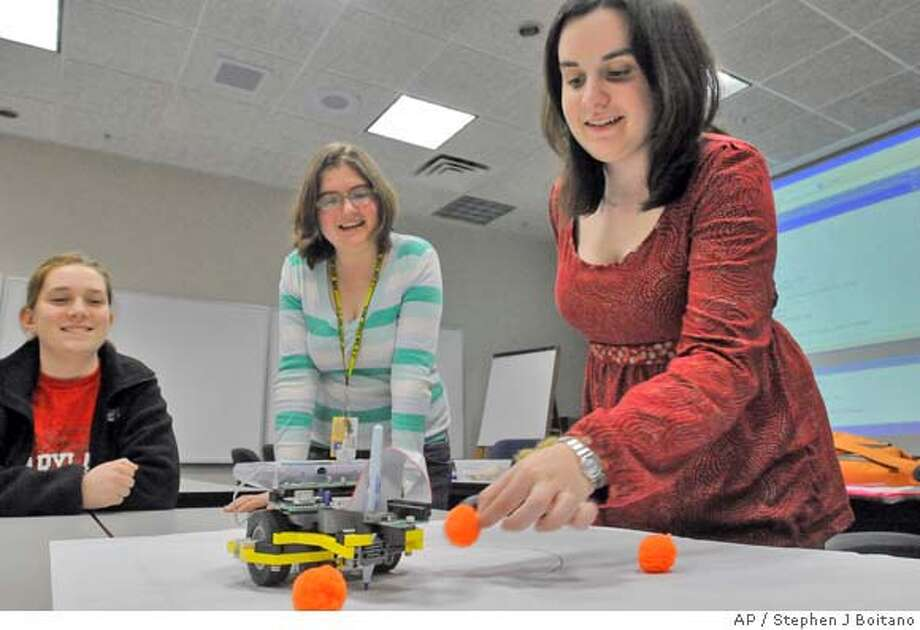 Left to right, Megan Hayes, 15, of Montgomery Village, Md., Julia Chartove, 15, of Bethesda, Md. and Dana Reback, 16, of Bethesda, perform a robotics experiment during an Engineering Exploring Program meeting at Lockheed Martin, Wednesday, Feb. 13, 2008 in Gaithersburg, Md. The aerospace and defense sector is reaching out to young American students as a generation of Cold War scientists and engineers hits retirement age and not enough qualified young Americans seek to take their place. (AP Photo/Stephen J. Boitano) Photo: Stephen J Boitano