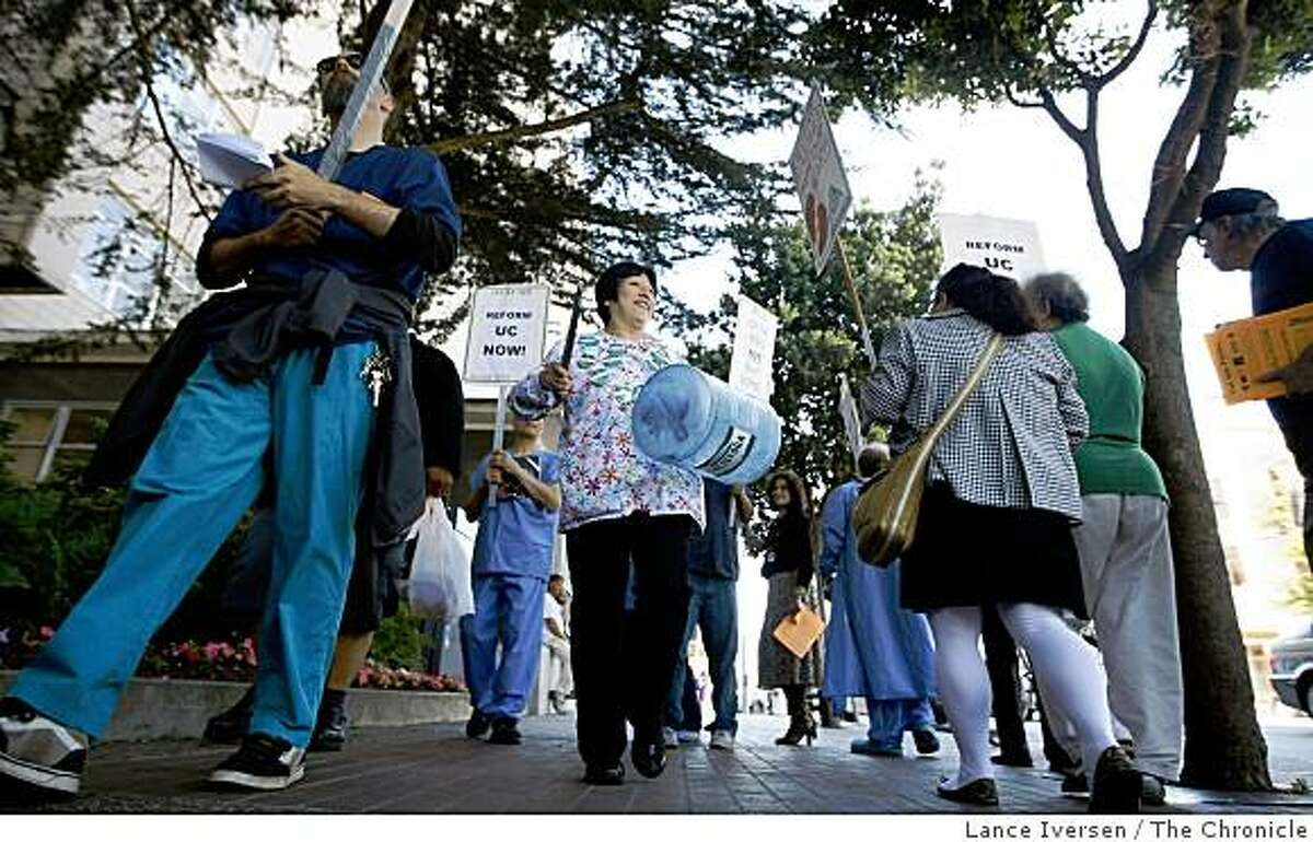 Beatriz Valencia beats on a water jug as she takes part in a University of California Professional & Technical Employees Local 9119 demonstration outside UCSF Tuesday July 14, 2009