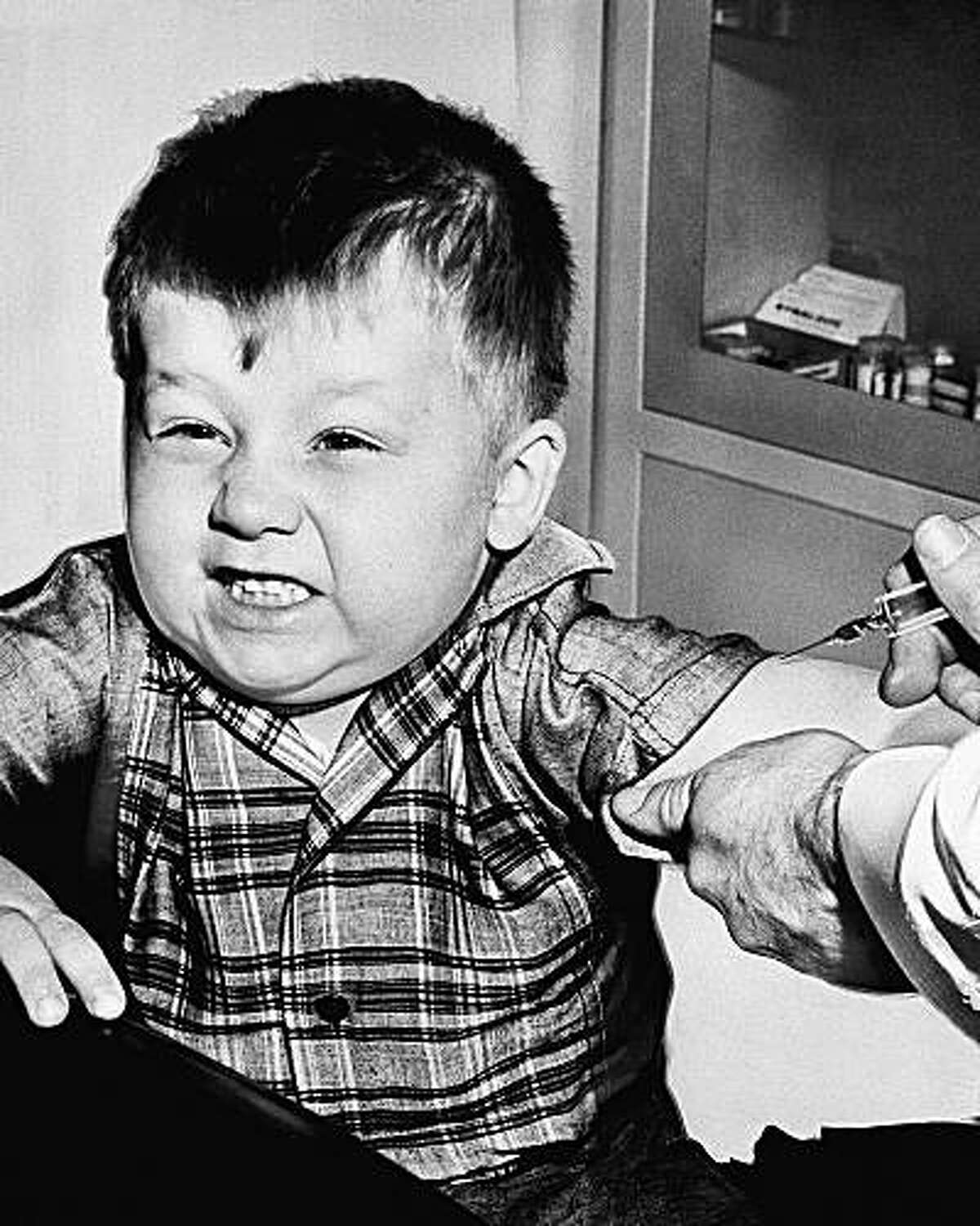 Three-year-old Jeffery Trzeciak grimaces bravely as a doctor prepares to give him an anti polio inoculation in New Kensington, Pa., Feb. 23, 1957. The shots were given as part of