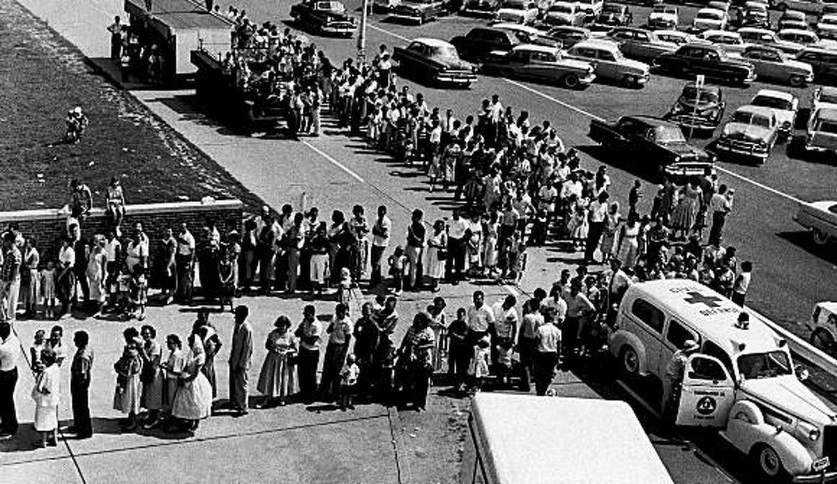 The line of people awaiting polio shots at Evansville's Municipal Stadium was still long four hours after the clinic started, when this picture was taken, Aug. 9, 1959. During the eight-hour program, about 14,000 from Evansville and surrounding communities received shots. (AP Photo)