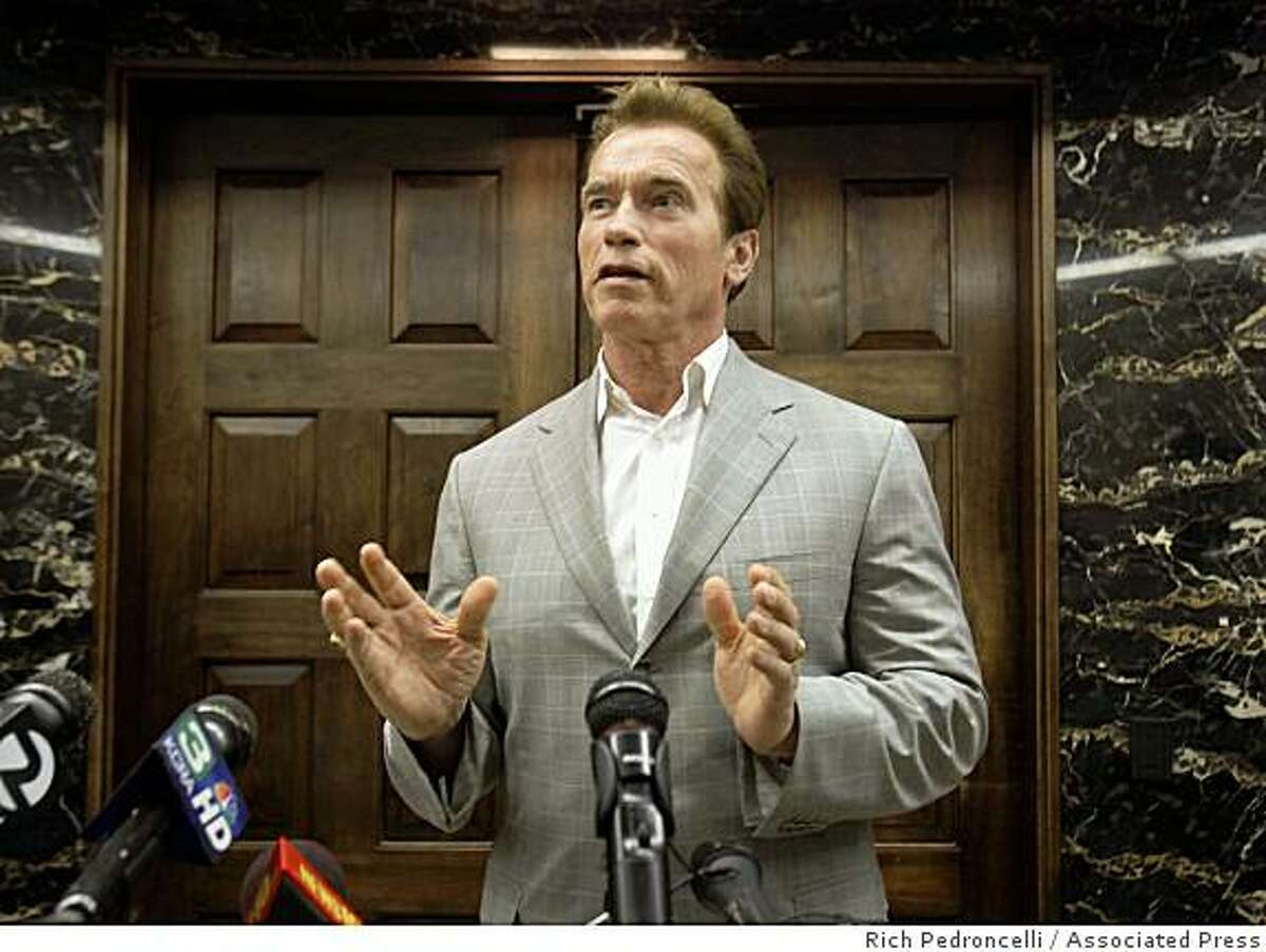 Gov. Arnold Schwarzenegger talks with reporters after during a break in budget meeting with Legislative leaders at the Capitol in Sacramento, Calif., Friday, July 10, 2009.