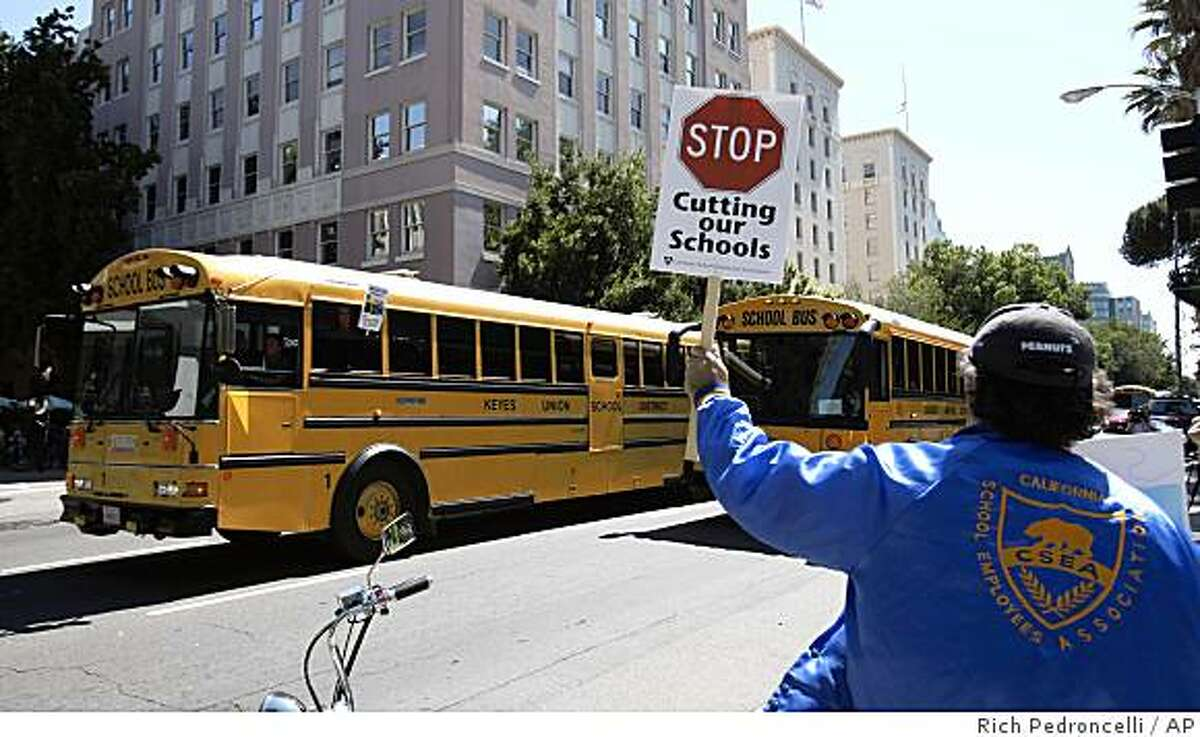 Raul Perez, of member of the California School Employees Association from Fresno, holds up a sign to show his support as dozen's of school buses circled the state Capitol in a demonstration against Gov. Arnold Schwarzenegger's proposal to cut state funding for buses, in Sacramento, Calif., Monday, July 13, 2009. Schwarzenegger met with Legislative leaders over the weekend to try to resolve the state budget stalemate. (AP Photo/Rich Pedroncelli)