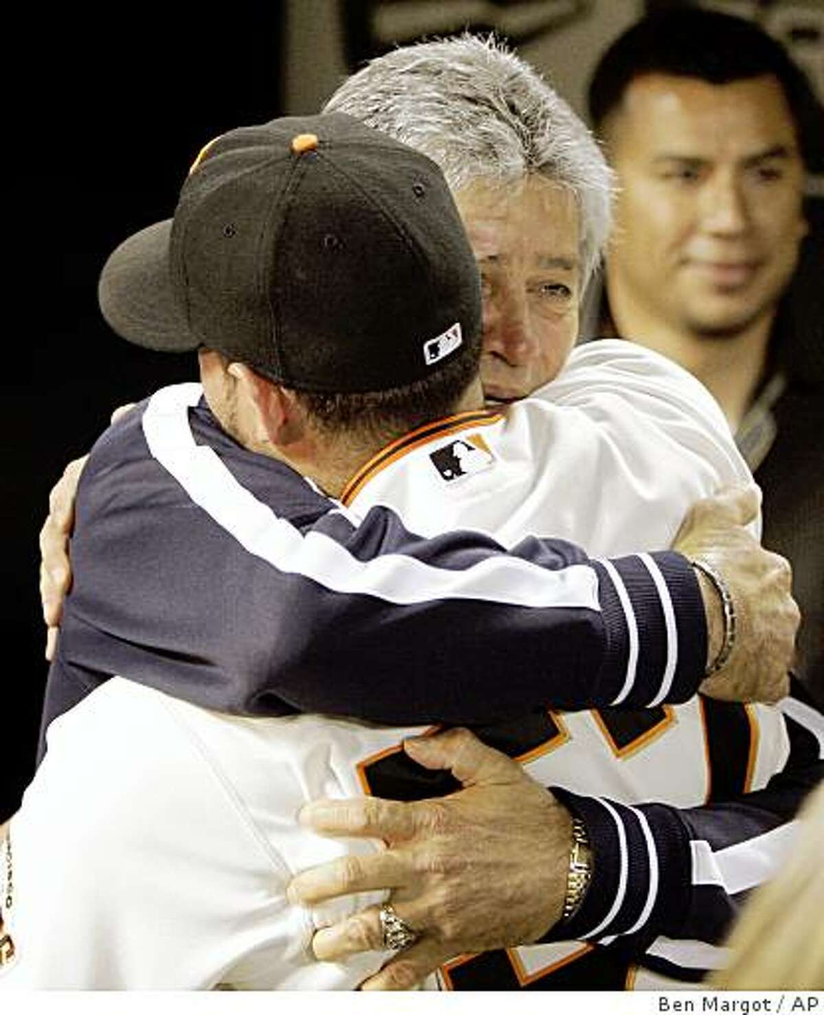 """San Francisco Giants' Jonathan Sanchez, left, is embraced by his father, Sigfredo Sanchez, at the end of a baseball game after pitching a no-hitter against the San Diego Padres Friday, July 10, 2009, in San Francisco. Sanchez said his father arrived in San Francisco the previous night. """"This is the first time he has seen me pitch. This is a gift for him,"""" said Sanchez, """"I feel awesome."""" (AP Photo/Ben Margot)"""