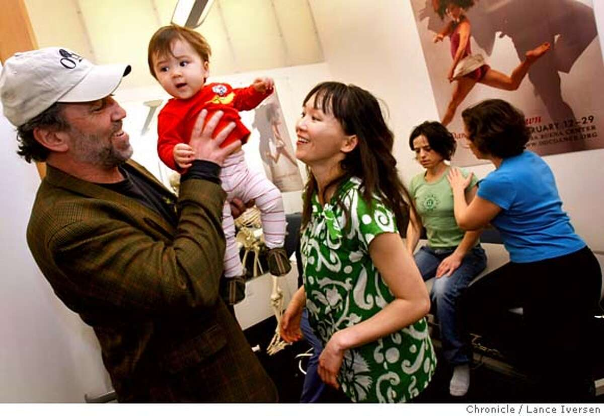 ###Live Caption:Dr. R. Richard Coughlin, founder of the free clinic at ODC Dance Commons in the Mission, takes over the parenting duties of ten-month-old daughter, Hanae Cricket Kambara-Coughlinis from his wife, professional dancer Yayoi Kambara during a visit to the clinic. In the background, yoga instructor Andrea Ferrance is being treated for neck pain by phyisical therapist Kendall Alway. Tuesday March 4, 2008 in SAN FRANCISCO. Photo By Lance Iversen / San Francisco Chronicle.###Caption History:Dr. R. Richard Coughlin, founder of the free clinic at ODC, takes over the parenting duties of the couples daughter ten-month-old, Hanae Cricket Kambara-Coughlinis from his wife, professional dancer Yayoi Kambara during a visit to the clinic were Andrea Ferrance a yoga instructor is being treated for neck pain by Kendall Always a physical Therapist. Tuesday March 4, 2008 in SAN FRANCISCO. Photo By Lance Iversen / San Francisco Chronicle.###Notes:Iversen 415-297-9395 CQ Ferrance Alway###Special Instructions:MANDATORY CREDIT PHOTOG AND SAN FRANCISCO CHRONICLE/NO SALES MAGS OUT