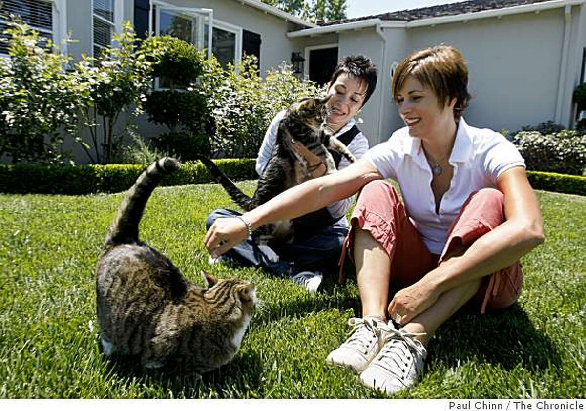 Jennifer France (right) and her partner Pouneh Toutounchian play with their cats in the front yard of their home in San Carlos, Calif., on Thursday, July 2, 2009. The couple has been unable to refinance their home with a 30-year loan despite drawing good incomes from their self-employed businesses.