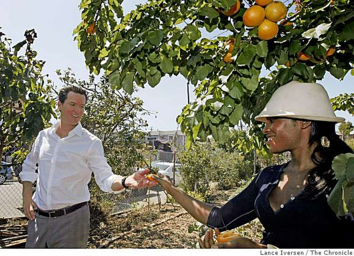 Abeni Ramsey a west Oakland Community Farm Coordinator hands Mayor Newsom a ripe apricot during his tour of Wow West Oakland Woods Farm. Wednesday July 8, 2009