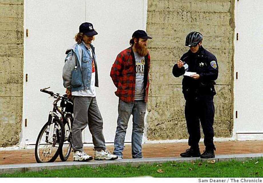 A police officer handcuffs and arrests two men in UN Plaza Thursday in an effort to enforce a safe crime-free environment in the area. (CHRONICLE PHOTO SAM DEANER) NOTE: I was told by a bystander the men were arrested for selling dope but when i made the photograph i did not think it went w/ the story based on my photoassignment sheet so i did not get id's or details. fyi. Photo: Sam Deaner, The Chronicle