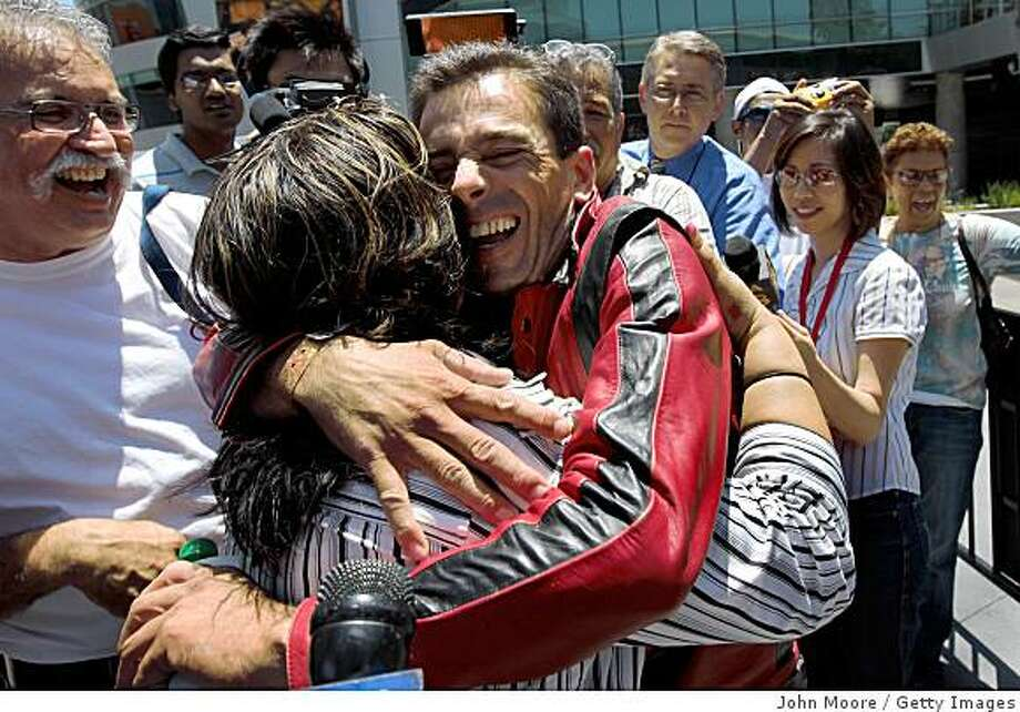Michael Jackson fan Melvin Price, from Earls Barton (R) in North Hampton, England hugs Barbara Ramirez after Ramirez gave him a free ticket to the Jackson memorial service at the Staples Center on July 6, 2009 in Los Angeles, California. Ramirez had won a pair of tickets in the online lottery, but gave one away, as a good samaritan. Some 17,500 are expected to attend Tuesday's event, out of a total of 1.6 million people who registered online for the event. Photo: John Moore, Getty Images