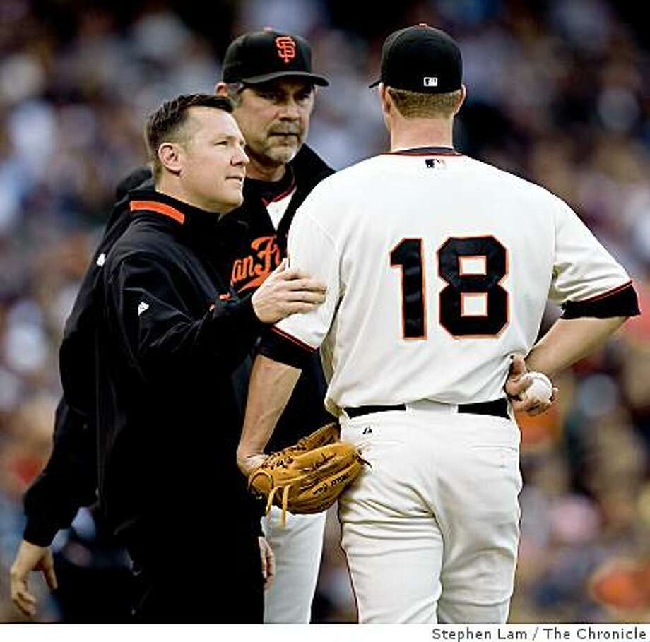 Matt Cain (18) of the San Francisco Giants speaks to Head Athletics Trainer Dave Groeschner, left, and manager Bruce Bochy, center  after being hit in the elbow by a line drive in the second inning against the San Diego Padres at AT&T Park Saturday, July 11, 2009. Photo: Stephen Lam, The Chronicle