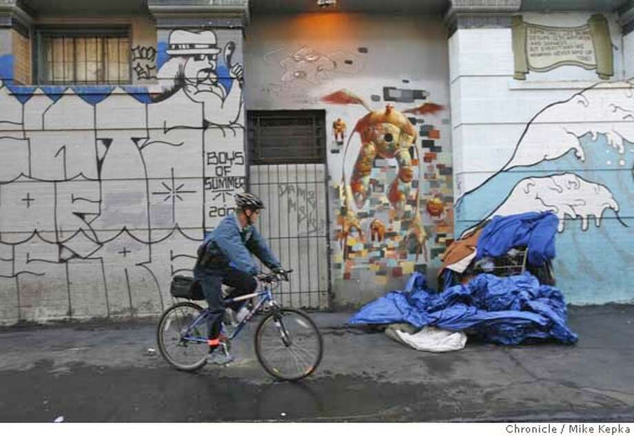 San Francisco probation officers, Darrin Dill checks on a pile of stuff belonging to homeless clients in the Tenderloin. Dill says the bike allows him to accessible to people who spend most of their time in streets. Mike Kepka / The Chronicle MANDATORY CREDIT FOR PHOTOG AND SAN FRANCISCO CHRONICLE/NO SALES-MAGS OUT Photo: Mike Kepka