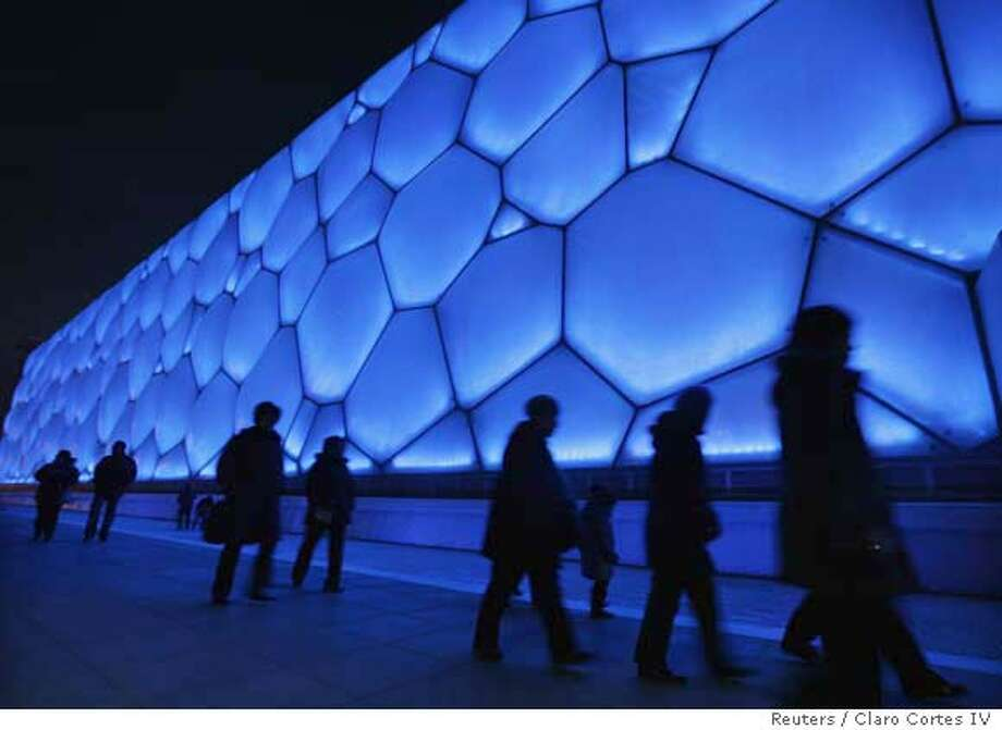 """Visitors walk outside the National Aquatics Centre, nicknamed the """"Water Cube"""", during the Good Luck Beijing 2008 Swimming China Open, in Beijing February 1, 2008. A blue box beating with a green heart, Beijing's 'Water Cube' National Aquatics Centre is the product of design and engineering harmony, and a rising power's desire to announce itself to the world. The $143-million venue for swimming, diving and synchronised swimming at the Beijing Games opened with a test event on Thursday allowing the Chinese capital's residents to ponder the ethereal cuboid structure at close range for the first time. REUTERS/Claro Cortes IV (CHINA) 0 Photo: CLARO CORTES IV"""