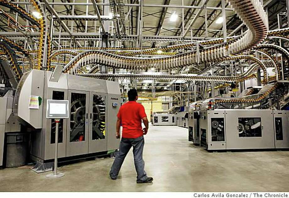 A Transcontinental production technician watches for errors in the conveyer gripper system during a printing test run. The 2-mile long delivery system moves papers from the printing presses to the post-pressroom where various sections and inserts are combined for delivery to subscribers. Photos of the new San Francisco Chronicle printing presses run by Transcontinental in Fremont, Calif., on Thursday, June 18, 2009, during a parallel practice run. Photo: Carlos Avila Gonzalez, The Chronicle