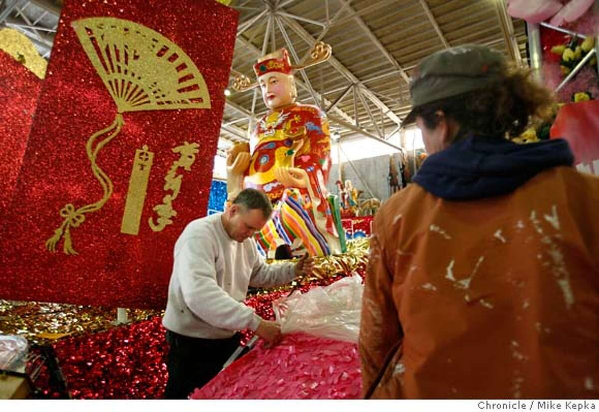 Inside a warehouse near pier 27, Master Float designer, David Thomas (center) of East West Productions puts the finishing touches on a Chinese New Years Parade float on Friday, Feb. 22, 2008 in San Francisco, Calif. Photo by Mike Kepka / San Francisco Chronicle Ran on: 02-23-2008 Designer David Thomas (center) finishes a float for the Chinese New Year Parade. He sealed electronic systems and loudspeakers with plastic. Ran on: 02-23-2008 Designer David Thomas (center) finishes a float for the Chinese New Year Parade. He sealed electronic systems and loudspeakers with plastic.