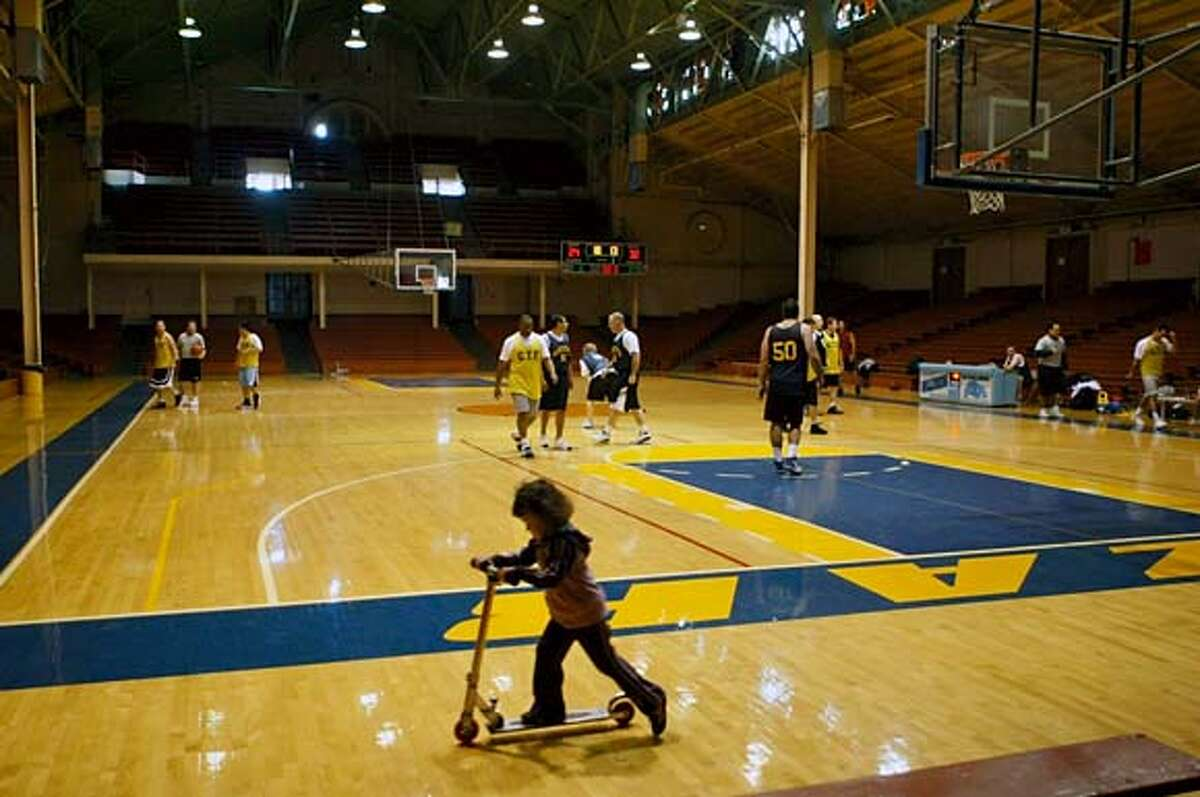 kezar_031_df.jpg A girl rides a scooter around Kezar Pavilion during a basketball game of SFPD officers. The building is in a state of disrepair. Photographed in San Francisco on 2/6/08. Deanne Fitzmaurice / The Chronicle Mandatory credit for photographer and San Francisco Chronicle. No Sales/Magazines out.