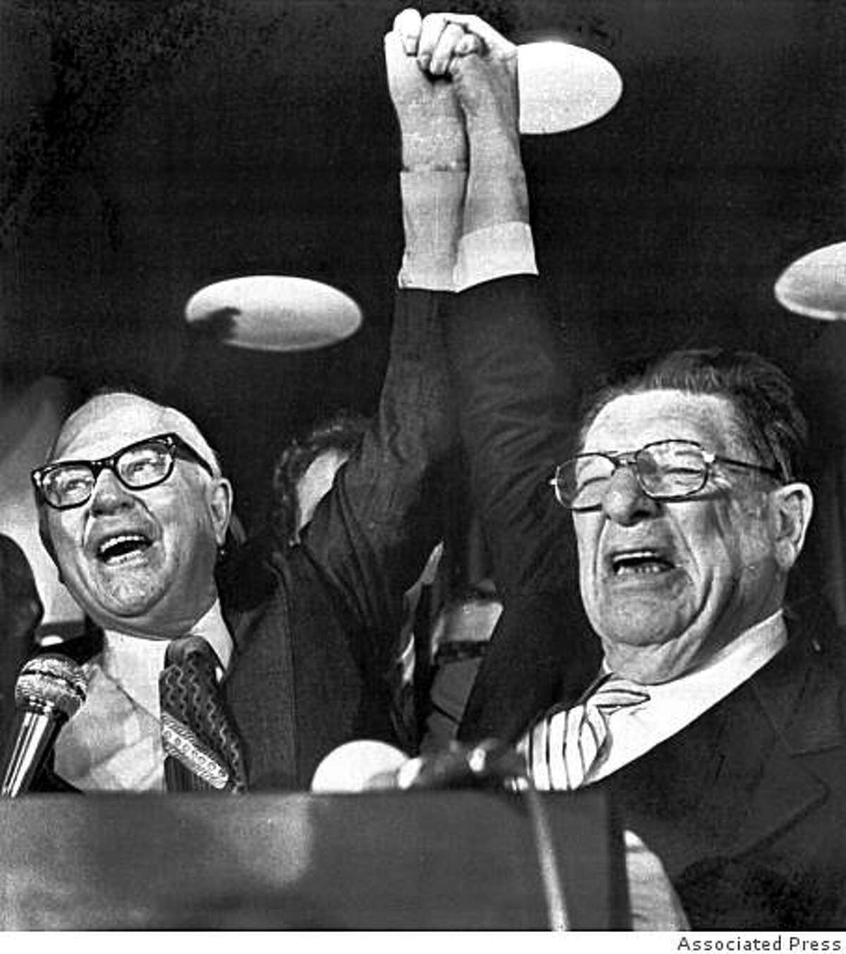 Paul Gann, left, and Howard Jarvis, hold up their hands on the night of June 7, 1978, as their co-authored initiative Proposition 13, took a commanding lead in the California primary.The Proposition provides monumental tax relief to peroperty owners. (AP Photo/stf)