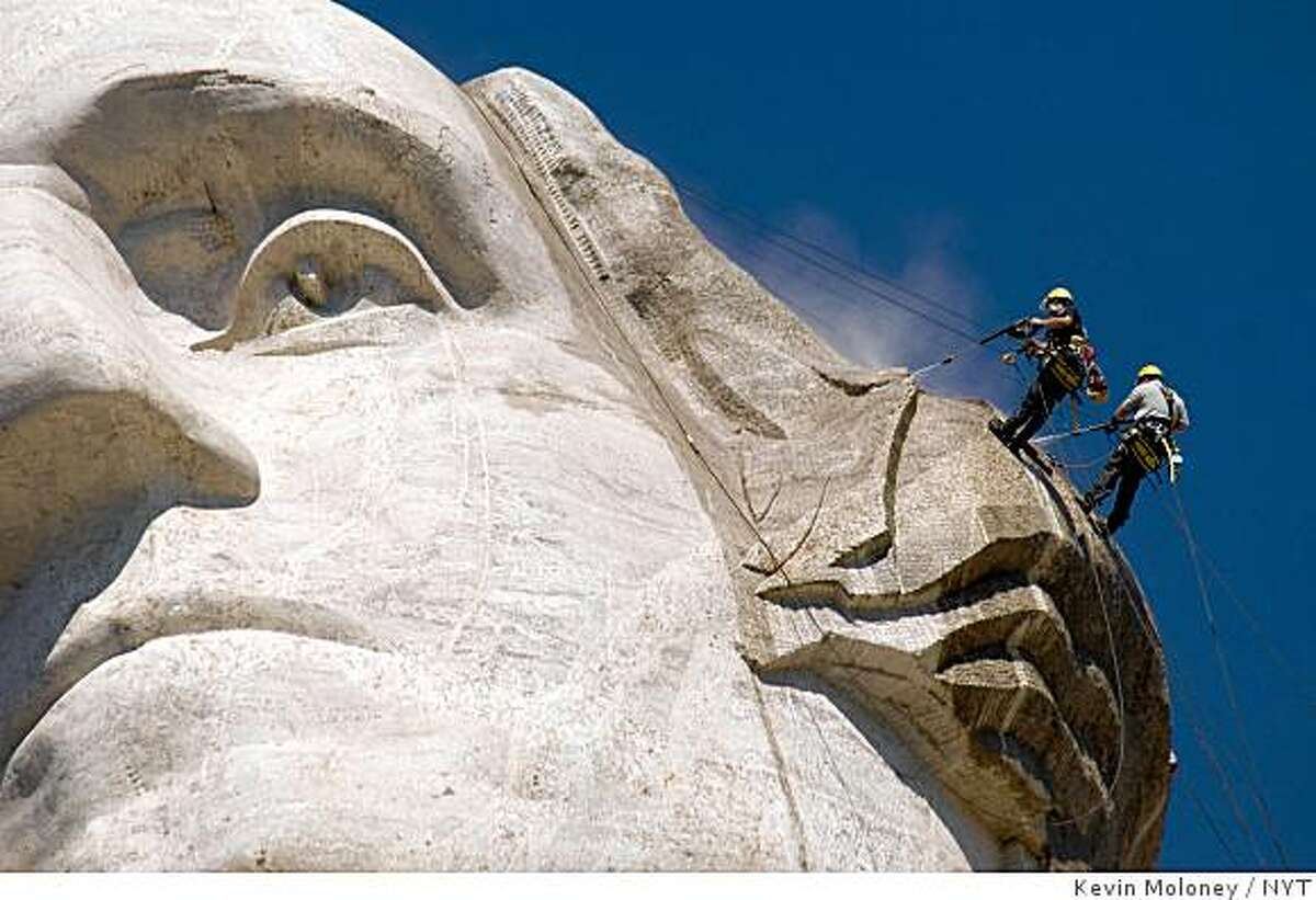 Workers cleaning George Washington's face from the Mount Rushmore National Monument on Friday, July 22, 2005.