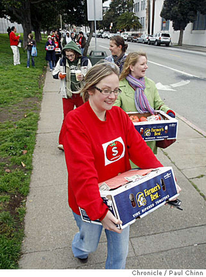 Suzanne Webb, an employee of the Cash Tomato website, brings more tomatoes to the masses. The Cash Tomato website stashed and handed out free money to people near Dolores Park in San Francisco, Calif., on Saturday, Feb. 23, 2008. The video sharing internet site gave away between $3,000 - $4,000 attached to about 1,000 tomatoes and hid them around the perimeter of the park and handed them pedestrians and motorists at 18th and Dolores.  Photo by Paul Chinn / San Francisco Chronicle Photo: Paul Chinn