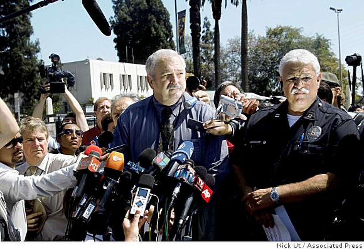 Craig Harvey, center, operating chief officer of the Los Angeles County Coroners office, gives a briefing on the results of the autopsy on the body of Michael Jackson, during a news conference Friday, June 26, 2009, in Los Angeles. Harvey says determining the cause of Jackson's death will require further tests that will take six to eight weeks. Harvey says there were no signs of foul play or trauma to the body. Officer Gus Villanveua stands at right.