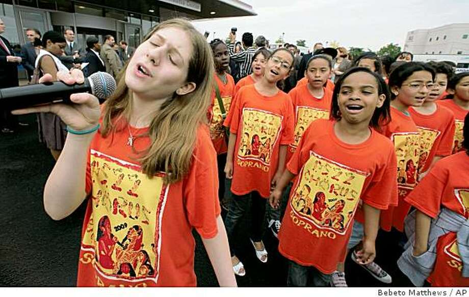 Alexandra Stein, 11, left, takes the microphone for a solo as Public School 22 Chorus members sing, during a building dedication at the Staten Island University Hospital in New York, Friday June 26, 2009. The New York fifth-grade chorus that first appeared on an online video has become world-famous, a cyber-phenomenon touted by top media outlets, celebrities and politicians. (AP Photos/Bebeto Matthews) Photo: Bebeto Matthews, AP