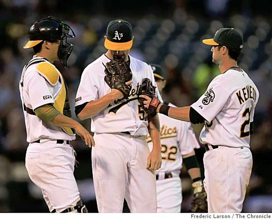 Oakland Athletics' starting pitcher Dallas Braden (middle) was consoled by A's Adam Kennedy (right) and Kurt Suzuki, before being removed in the 6th inning after giving up 6 runs against the Colorado Rockies at the Oakland-Alameda County Coliseum on June 26, 2009. Photo: Frederic Larson, The Chronicle