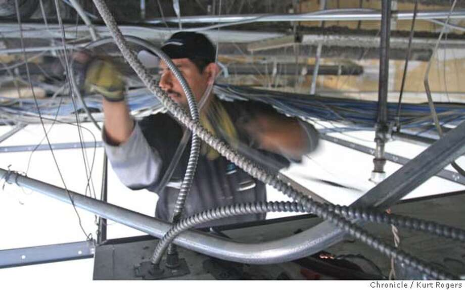 Alberto Hernandez strips a building of all its wiring before it can be up graded to code.  Silicon Valley is losing it's middle wage jobs as it turns out that their are jobs that pay pretty well one of those jobs is electricians.  Photo By Kurt Rogers / The Chronicle Photo: Kurt Rogers