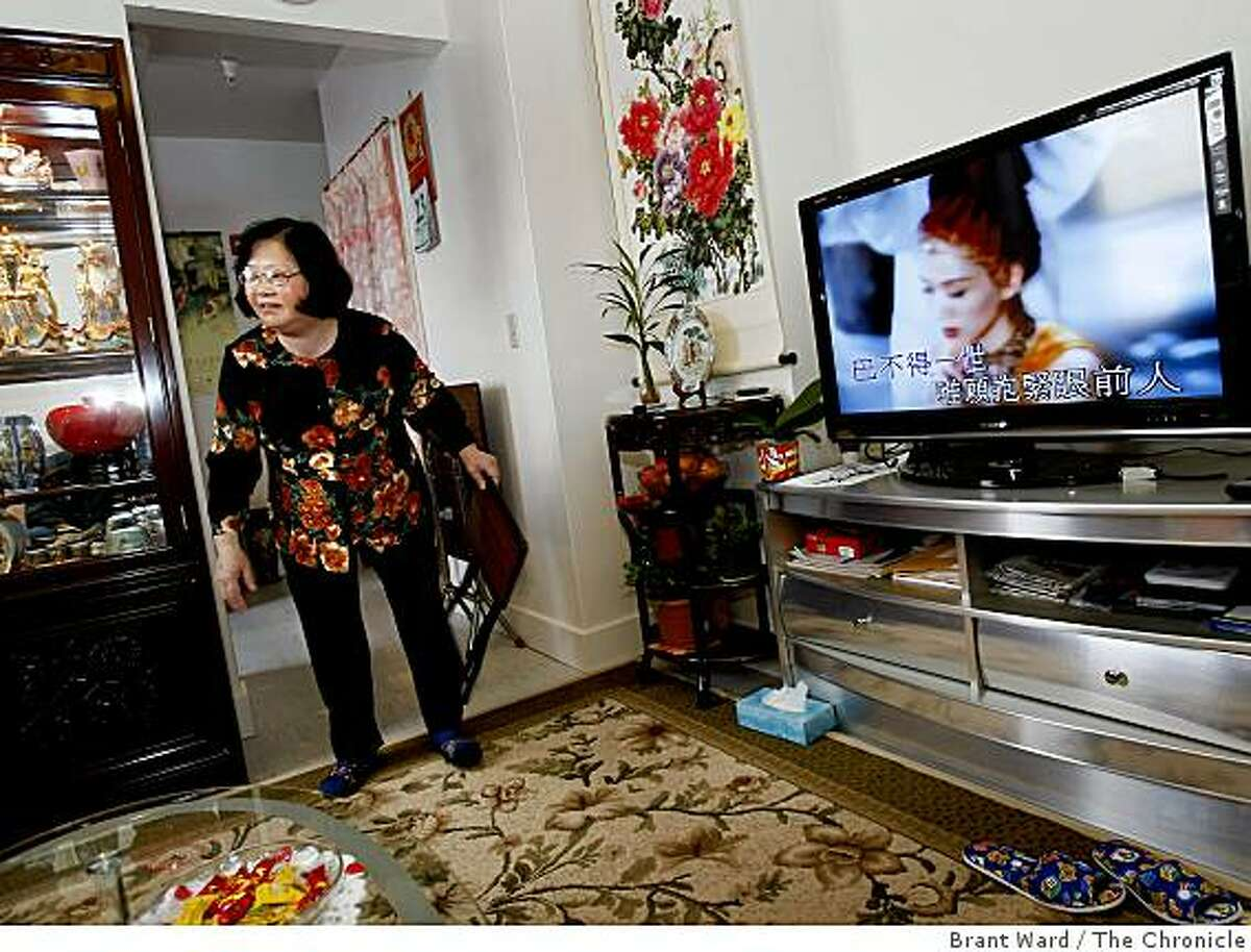 Ru Mei Peng, Ji's wife, is pleased with her renovated apartment which includes a bright living room. Residents at 53 Columbus Avenue near San Francisco's Chinatown are celebrating their new homes after the SF Community Land Trust helped with renovations.