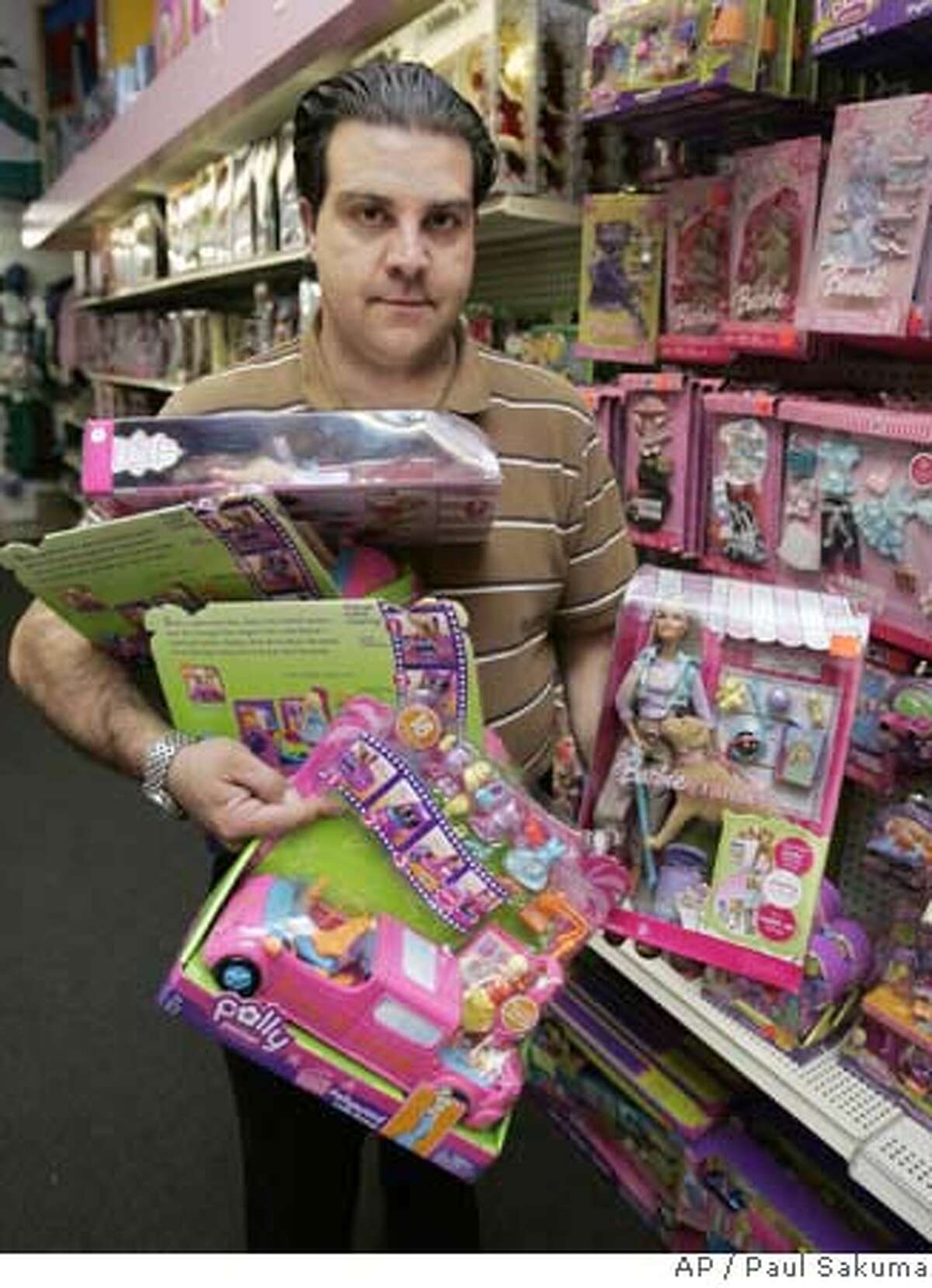 FILE - Keith Schumacker holds up the Polly Pocket Pollywood Limo-Scene, left, and the Barbie Tanner set, right, at Talbots Toyland in San Mateo, Calif., Tuesday, Aug. 14, 2007.