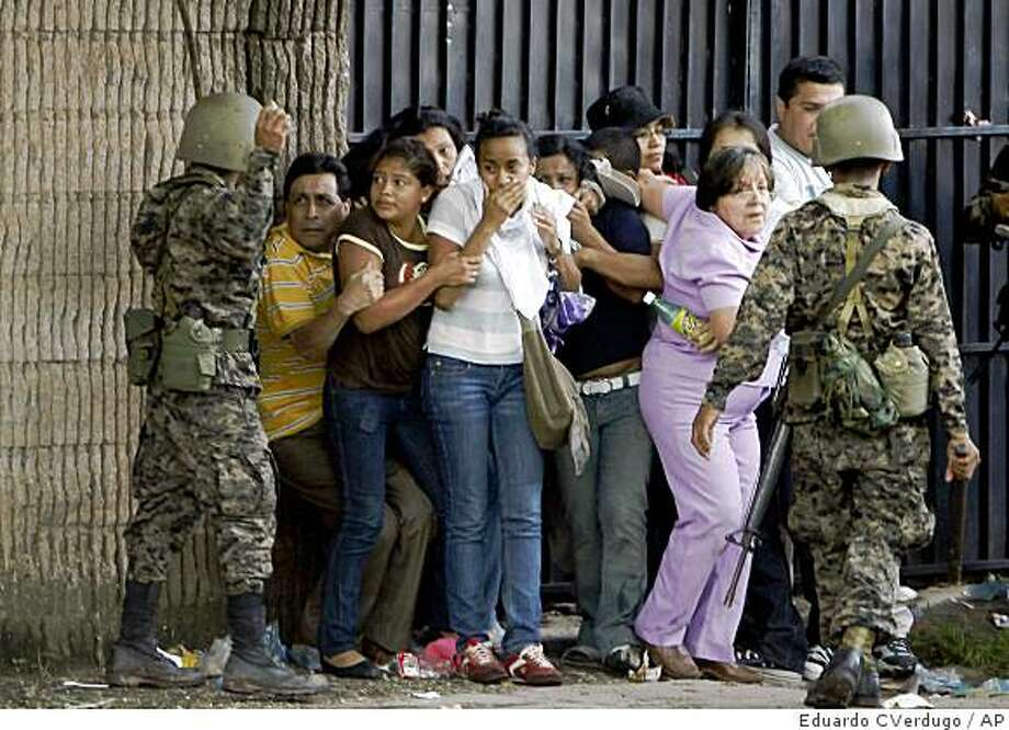 Honduran army soldiers surround a small group of supporters of ousted Hoduran President Manuel Zelaya after violence broke out near the presidential residency in Tegucigalpa, Honduras Monday June 29, 2009. Photo: Eduardo CVerdugo, AP