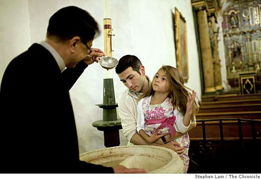 From left, Pastor Arturo Albano, James Irwin, center, godfather to four-year-old Amaya Fabio, right, practices baptism procedures inside Mission Dolores in San Francisco, Calif. on Friday, June 26, 2009.