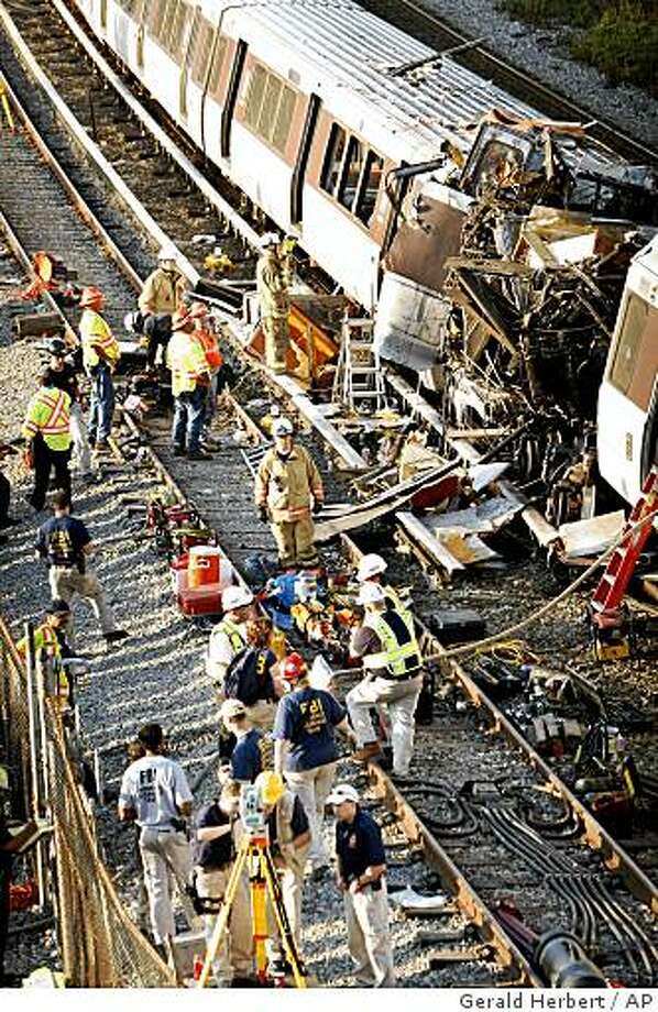 Investigators and officials look over the collision scene of two Metro transit trains in Northeast Washington, Tuesday, June 23, 2009. (AP Photo/Gerald Herbert) Photo: Gerald Herbert, AP