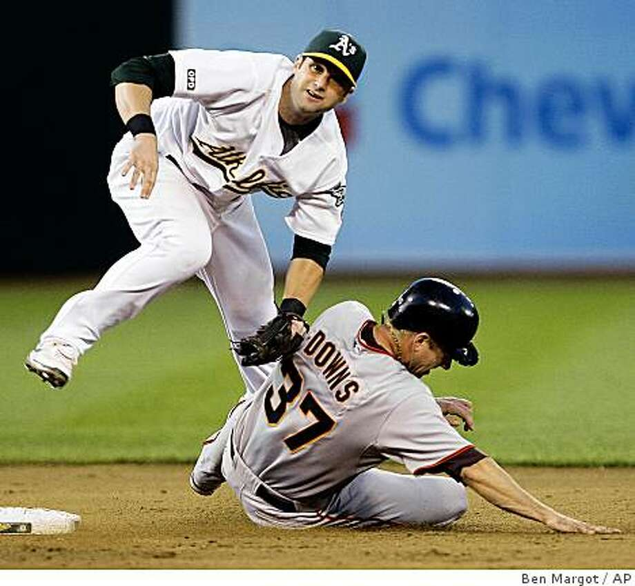 Oakland Athletics second baseman Adam Kennedy hops over San Francisco Giants' Matt Downs (37) after completing a double play in the fifth inning of a baseball game Monday, June 22, 2009, in Oakland, Calif. Giants' Aaron Rowand was out at first base.  (AP Photo/Ben Margot) Photo: Ben Margot, AP
