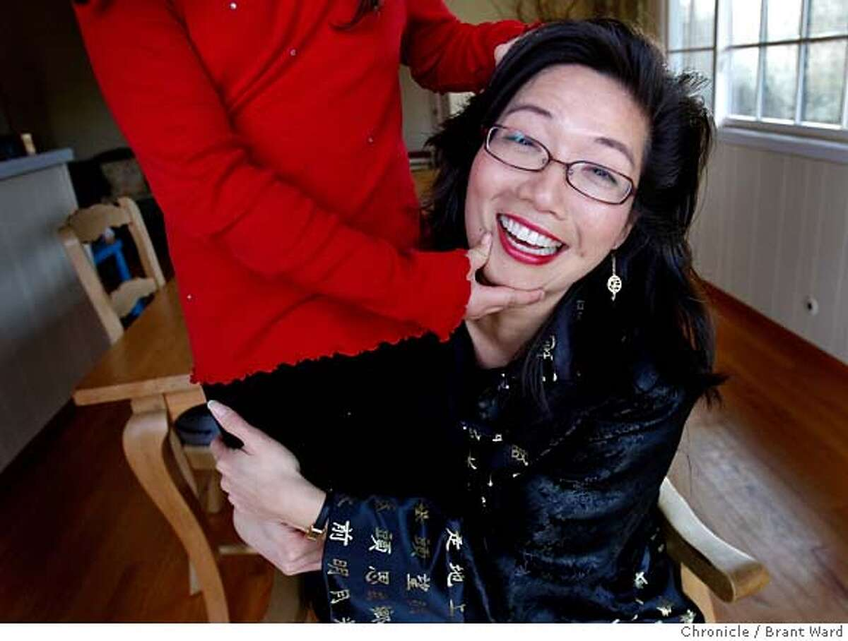 """One of Lo Mei Seh's children, who was adopted from China, has fun showing her mom how to pose. Lo Mei Seh is upset with a trailer from the movie """"Juno"""" which said """"Why didn't you go to China? I hear they give babies out like iPods."""" (By Brant Ward/San Francisco Chronicle)"""