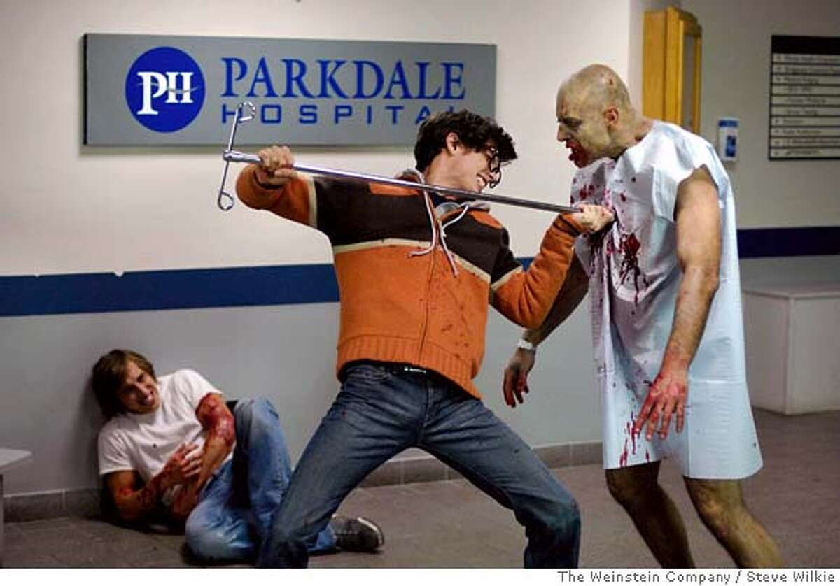 """In this image released by The Weinstein Company, Chris Violette, who plays Tony, left, lays wounded as Joe Dinicol, who plays Eliot, center, fights off a zombie in the film, """"George A. Romero's Diary Of The Dead."""" (AP Photo/The Weinstein Company, Steve Wilkie) ** NO SALES ** IMAGE RELEASED BY THE WEINSTEIN COMPANY. NO SALES. AP PROVIDES ACCESS TO THIS PUBLICLY DISTRIBUTED HANDOUT PHOTO. THE COPYRIGHT IS OWNED BY A THIRD PARTY."""
