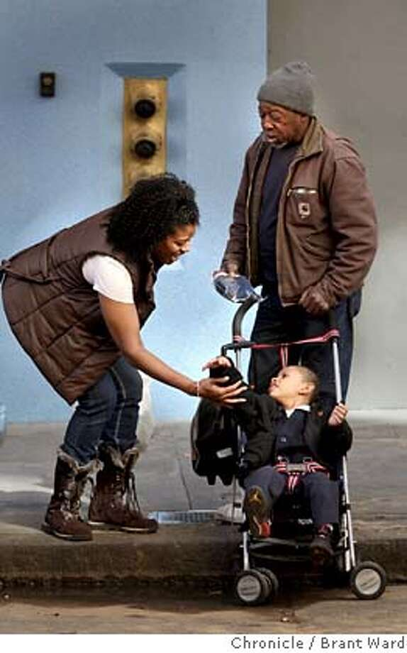 Toni Duke greets 4 year old Dwight Hall after giving his godfather James Johnson, right, a bag of warm things. Her daily drive through the Tenderloin district inspired her to help with gloves, hats, etc to help the homeless stay warm in the winter. (Photo by Brant Ward/San Francisco Chronicle)  Ran on: 02-14-2008  Toni Dukes greets 4-year-old Dwight Hall after giving his godfather, James Johnson (right), a bag of warm things. Photo: Brant Ward