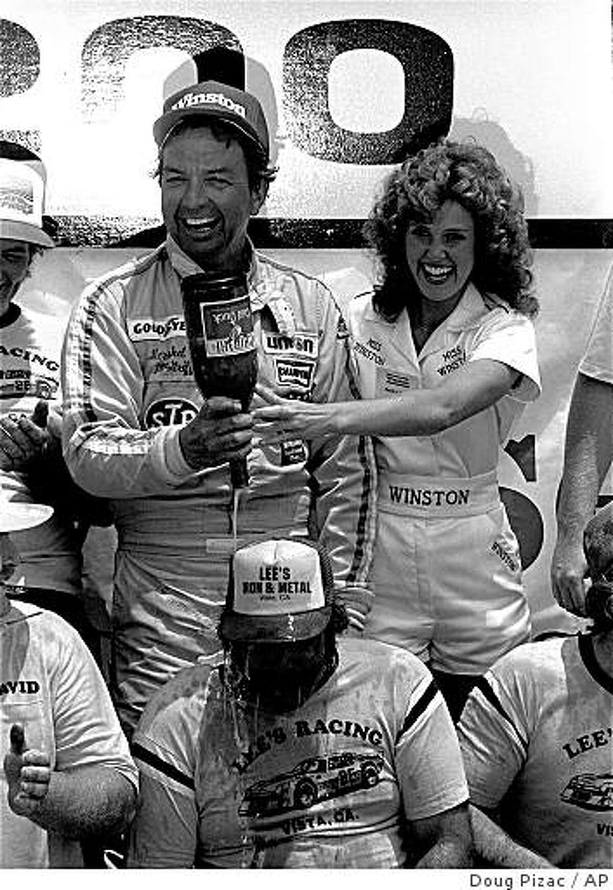 Hershel McGriff, left, of Bridal Veil, Ore., empties a bottle of Cold Duck over the head of crew member Snow Thornsberry with the help of Miss Winston Becky Carter after winning the Warner Hodgdon 200 NASCAR race at Riverside Raceway . (AP Photo/Doug Pizac)