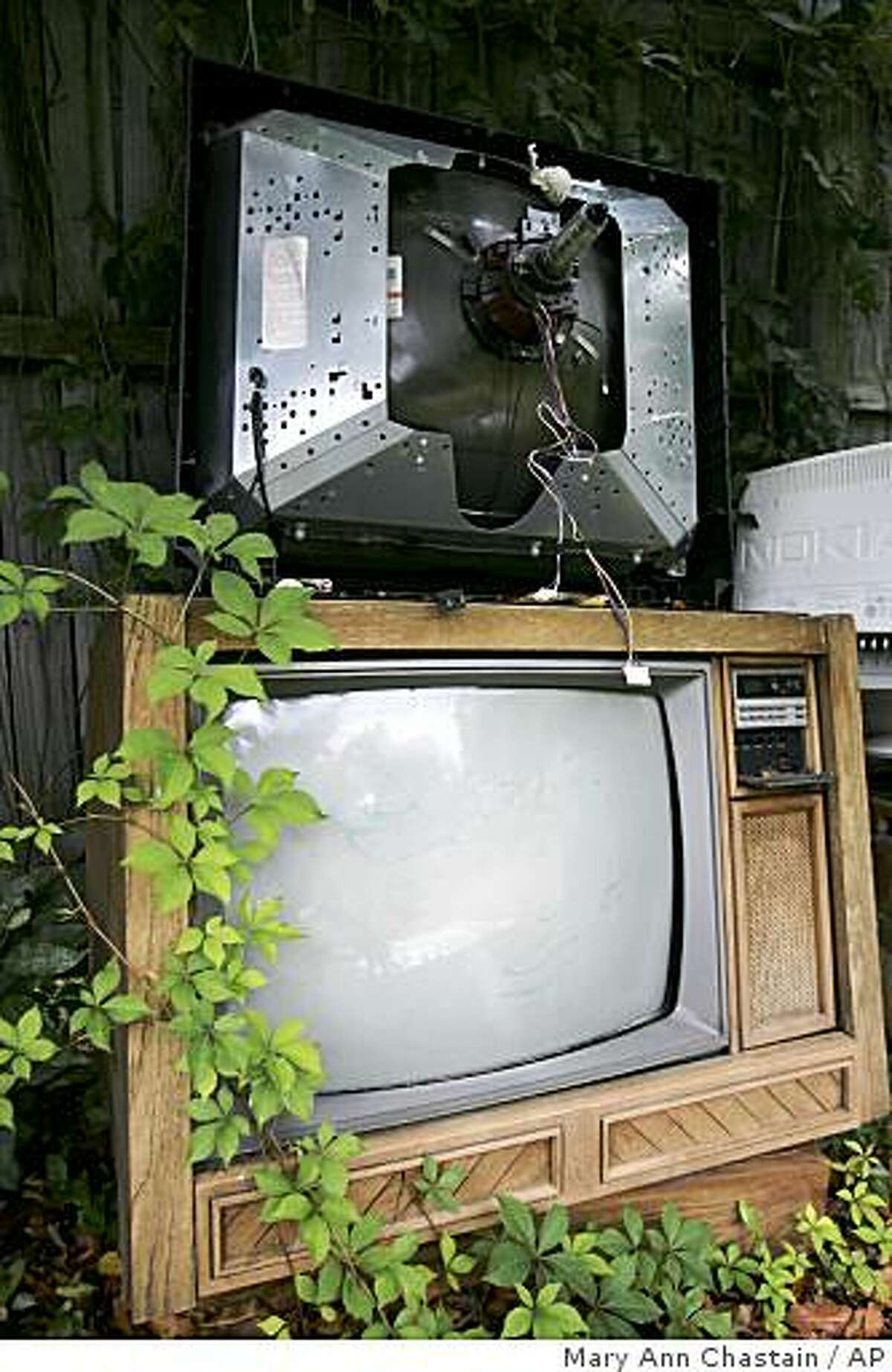 In this photo taken June 5, 2009, Ivy grows on an old console television that has been abandon at Randy's TV Repair in Lexington, S.C. Friday, June 5, 2009. The county will be switching from an analogue signal to digital Friday, June 12, making these old television inoperable unless it is connected to a converter box.(AP Photo/Mary Ann Chastain)