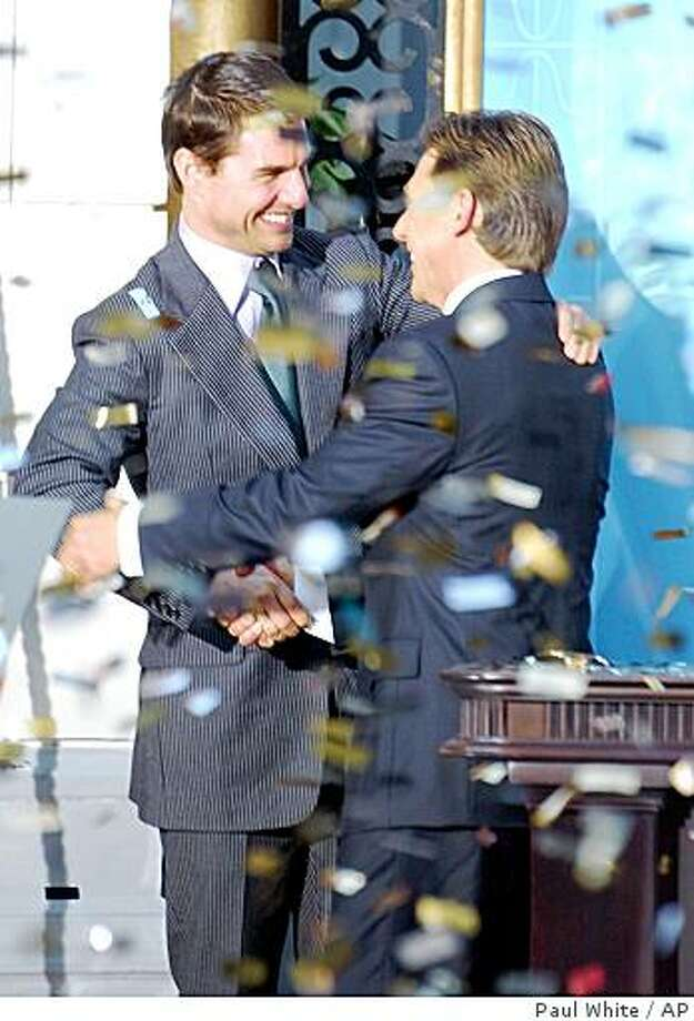 ** FILE **Confetti rains down as U.S. actor Tom Cruise, left, embraces David Miscavige, the Scienology Church's President of the Rulling Council during the official opening of a new Scientology church in central Madrid in this Sept. 18, 2004 file photo. Photo: Paul White, AP